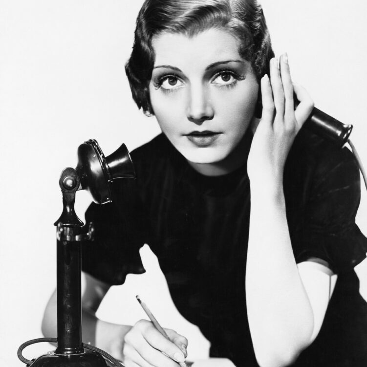 Portrait of woman on telephone taking notes